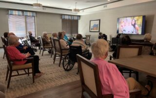 group activity senior living community event gathering common room sitting in chairs wedding on tv