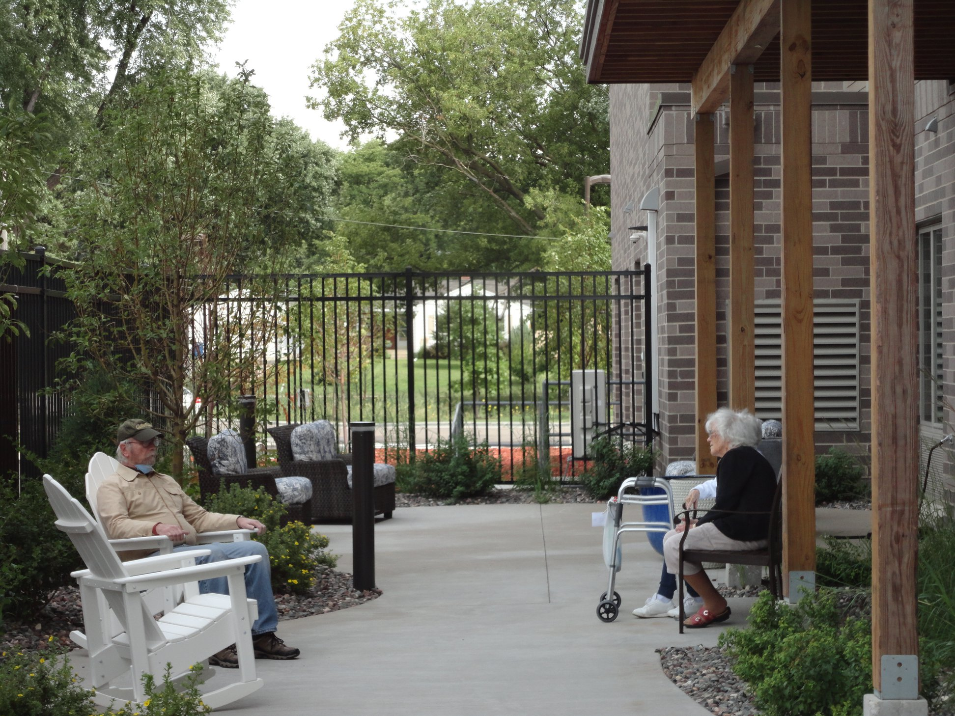 Senior living facility apartments outdoors woman and man sitting on patio minnesota