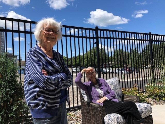 two women on patio sunshine summer outdoors patio furniture senior living community apartments memory care community