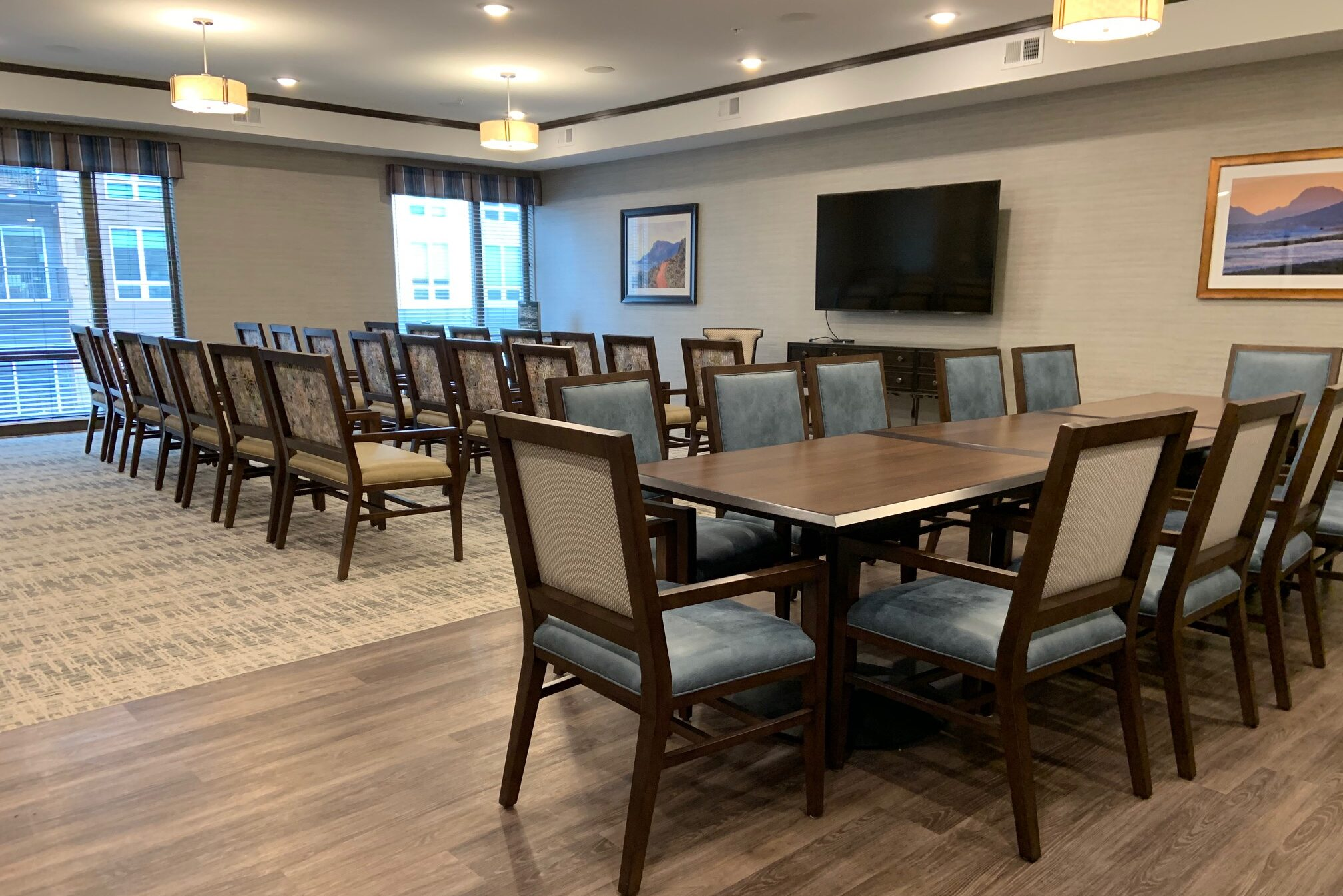Assisted living community room with tables, chairs and TV empty
